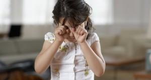 Girl (4-6) rubbing eyes, crying